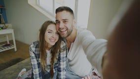 Pov-skott av gulliga och älska par som talar den hållande smartphonen för online-video pratstund och pratar till vänner som sitte Arkivfoton