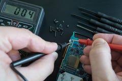 Pov-skottet av teknikerhänder mäter spänning, strömstyrka på den brutna smartphonen vid multimeteren med sonder Royaltyfri Foto