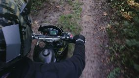 POV slow-motion shot of the rider`s hand and part of motard`s black motorcycle. POV slow-motion shot of a rider in a crash helmet and part of a black motard stock video footage