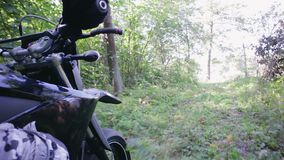 POV slow-motion shot of the rider`s hand and part of motard`s black motorcycle. Enduro racing through the woods during the race. Extreme entertainment on rough stock footage