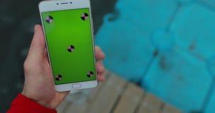 POV, smartphone masculin de participation de main avec l'écran vide marchant dans le pilier de ville