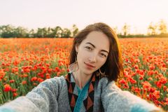 POV of smiling woman taking selfie in flower field. Point of view image of smiling beautiful young woman taking photo selfie in poppy flower field in summer stock images