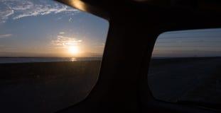 POV, solnedgång på havet till och med sidan och bakre fönster av bilen Arkivfoto