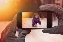 POV som tar bilden med smartphonen behandla som ett barn leka snow Fotografering för Bildbyråer