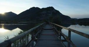 POV-standpunt die langs brug houten weg op meer bij zonsopgang in de zomer lopen Openlucht groene de aard scape wildernis van Eur stock video