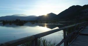 POV-standpunt die langs brug zij houten weg op meer bij zonsopgang in de zomer lopen De openlucht groene aard van Europa scape stock footage