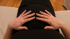 POV-standpunt van een zwangere vrouwenbuik die een verlovingsring dragen en haar baby binnen strelen stock video