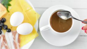 POV strzału żeńska ręka miesza woń ranku kawę z dojną używa łyżką cieszy się śniadaniowego jedzenie zbiory