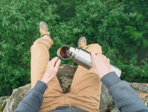 POV of traveler pouring tea from thermos Royalty Free Stock Photos