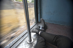 POV Traveler reclines in train carriage. Point of view of traveler, sitting on a moving train as the blurred scenery of Kolkata, India, passes by Stock Photos