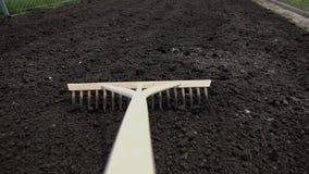 POV of using the rake on the black soil stock footage