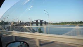 POV van de zetel van de taxipassagier bij de nieuwe brugbouw over de rivier in Kyiv stock video
