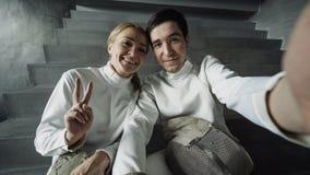 POV van Twee de jonge glimlachende schermersmens en vrouw die selfie op smartphonecamera nemen na het schermen binnen opleiding royalty-vrije stock afbeelding