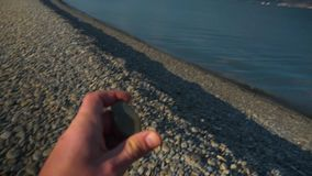 POV. Video from the first person. A man`s hand takes a smooth sea stone and throws it into the sea. In the background you can see the sea, the mountains and stock video footage