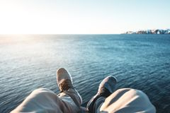 POV view of hipster legs and shoes on background of blue sea and snow mountains. Brave man traveler sitting on high cliff above ocean Stock Photos