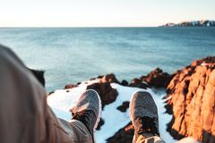 POV view of legs and shoes on background of snow rock and ocean. Brave explorer sits in front of snowy cliff and look on feet. Adventure and lifestyle Royalty Free Stock Photography