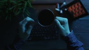 POV view of man drinking coffee and typing on keyboard. POV shot of man drinking coffee and typing on keyboard by office wooden table stock video footage
