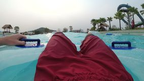 Pov view of Man floating on inflatable circle in the pool with artificial waves. CHONBURI, THAILAND, JANUARY 22, 2018: Pov view of Man floating on inflatable stock video footage