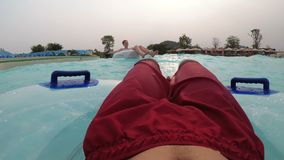 Pov view of Man floating on inflatable circle in the pool with artificial waves. CHONBURI, THAILAND, JANUARY 22, 2018: Pov view of Man floating on inflatable stock footage