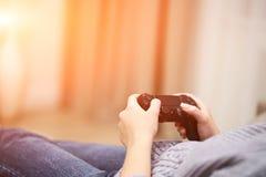 POV-Vrouw die op de bus voor TV liggen en in handen draadloze spelbesturing houden Het concept van de spelverslaving stock afbeeldingen