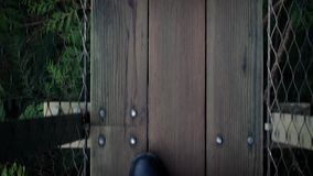 POV Walking On Forest Walkway. POV legs walking on wooden forest walkway above the trees stock footage