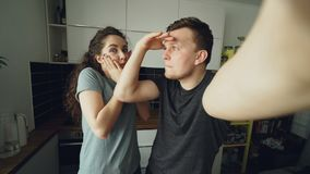 POV of Young funny couple taking selfie photos with smartphone camera standing in the kitchen at home in the morning. POV of Young funny couple taking selfie stock footage