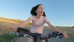 POV of a young girl enjoying a bicycle ride on the rural countryside stock video