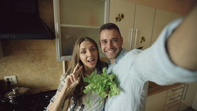 POV Young happy couple taking selfie picture while cooking breakfast in the kitchen at home. Young happy couple taking selfie picture while cooking breakfast in stock video footage