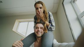 POV of happy smiling and beautiful couple take selfie portrait on smartphone camera while girl sitting on man`s neck at stock video footage
