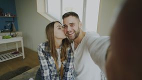 POV of Young smiling and beautiful couple take selfie portrait on smartphone camera and kiss while sitting on bed in the Royalty Free Stock Photography