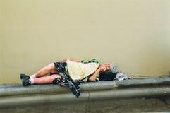 Povertà, donna homless che dorme sulla via fotografia stock