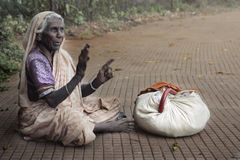 Poverty. Horizontal photo of the poor old woman sitting outdoors near her things Stock Image