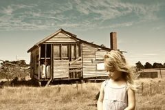 Poverty. Little girl in front of a derelict farm house