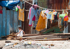 Poverty. A young Cambodian girl in a fishing village walks through trash and debris Royalty Free Stock Image