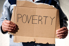 Poverty. Man holding up on  a cardboard sign with the word poverty Stock Photo