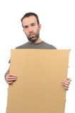 Poverty. A scruffy looking guy holding a cardboard sign, isolated on a white background Royalty Free Stock Photos