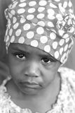Poverty. A poor little african american girl looks up at the camera with a very sad expression Royalty Free Stock Photography