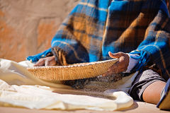 Poverty. Portrait of African woman with a basket sieve straining sorghum, staple food in Africa royalty free stock photos