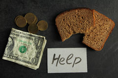 Poverty. The change and crumpled dollar near pieces of paper with inscription Help on a black background with pieces of bread . The concept of poverty stock photography