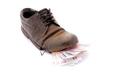 Poverty concept. Several one hundred South African Rand notes in a black old broken leather shoe of a hobo. Image isolated on white studio background Royalty Free Stock Image