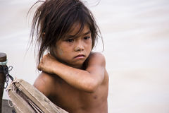 Poverty Girl. CAMBODIA – May 2012: A young poverty girl scratching herself on a rough wooden boat sailing in Tonle Sap Lake, Cambodia, May 2012.  Living Royalty Free Stock Images