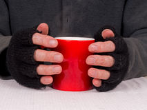 Poverty.hardship - poor man with hot drink. Warming hands round red mug of steaming tea or soup stock photo
