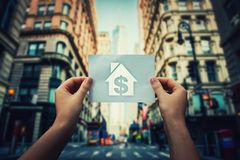 Poverty and homelessness. Global issue concept as woman hands holding a paper sheet with house and dollar icon inside in the middle of the street of a big city stock photography