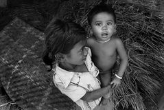 Poverty in India. October 09, 2011.Bastar, Chhattisgarh,Madhya Pradesh,India,Asia-A girl holding her brother in a tribal village of Bastar Stock Photography