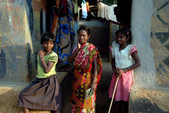 Poverty in India. October 29,2011 Nimdihi,Raghunathpur,Jharkhand,India,Asia-Women with two girl in-front their mud house in a remote village of Raghunathpur Royalty Free Stock Photography