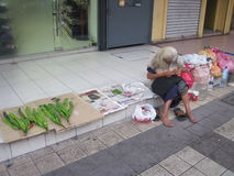 Poverty in Malaysia. An elderly woman selling vegetables Royalty Free Stock Images