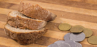 Poverty and misery. The composition on a wooden background, black bread and a little money Royalty Free Stock Images