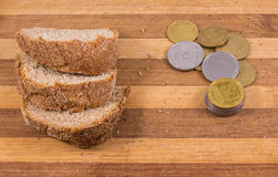 Poverty and misery. The composition on a wooden background, black bread and a little money Stock Photos