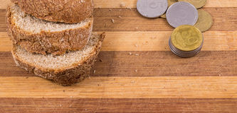 Poverty and misery. The composition on a wooden background, black bread and a little money Royalty Free Stock Photos