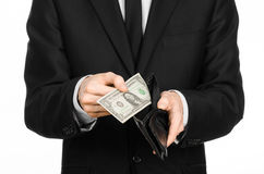 Poverty and money theme: a man in a black suit holding a empty wallet and banknote 1 dollar on white isolated background in studio Stock Photo
